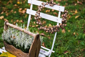 Wreath of acorns and wooden crate of heather on garden chair