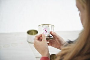 Girl sticking number onto tin can for DIY Advent calender