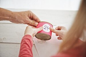 Hands sticking number on paper-covered tin can for DIY Advent wreath