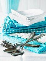 Verschiedene blaue und weisse Tücher, gestapelt, mit Besteck