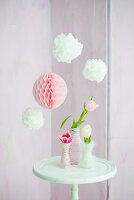 Pompoms and paper honeycomb ball above tulips in vases wrapped in cord