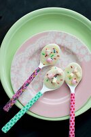 Colourful spoons covered with white chocolate and bright hundreds and thousands