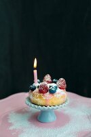 Doughnut decorated with fresh berries and birthday-cake candle