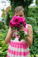 Girl wearing pink and white striped batik dress and holding pink roses