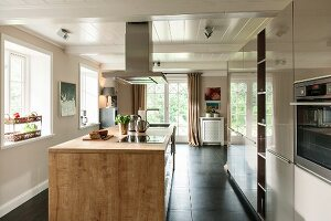 Wood-clad island counter in open-plan kitchen