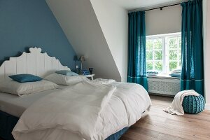 Bedroom with blue accents: double bed with white, carved headboard against blue-painted wall and blue, floor-length curtains
