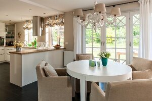 Round, white dining table and pale armchairs under chandelier in front of open-plan kitchen