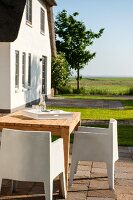 White, plastic, modern outdoor chairs and wooden table on summery terrace outside holiday home