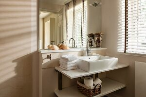 Washstand with countertop basin in corner of bathroom next to window with louvre blind