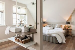 Narrow partition with integrated washstand in front of double bed in open-plan bedroom in shades of beige