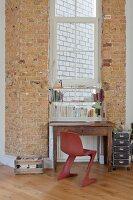 Old desk below window flanked by brick walls