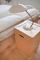 Retro lamp on cardboard bedside cabinet