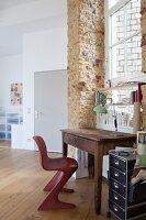 Old desk below window in brick wall