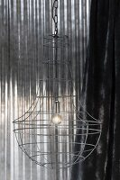 Wire lampshade in front of shiny metal background