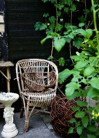 Vintage rattan chair and basket on terrace in garden against wooden wall
