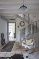 Fur blanket on rocking chair at foot of grey staircase in restored hallway