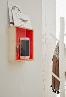 A wooden box painted orange as a mobile charging station