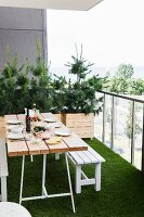 Set table and white bench on balcony with artificial grass floor and small conifers planted in wooden trough
