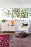 Leather pouffe in front of white armchair next to sideboard below bank of windows