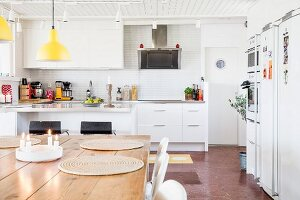 Place mats on wooden table below yellow pendant lamps in white fitted kitchen
