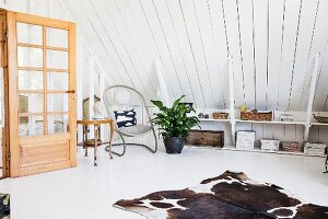 Cowhide rug on white floor in attic room with wood-clad sloping ceiling, shelves on knee wall and open interior door