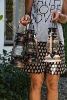 Woman carrying three vintage storm lamps