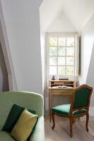 Writing desk and antique upholstered chair in niche below lattice dormer window