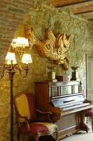 Piano and Baroque armchair against stone wall