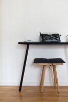 Typewriter on simple console table and wooden stool
