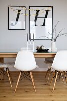 Shell chairs around dining table below framed letters on wall