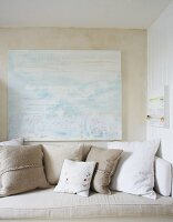 White and ecru cushions on bench below modern artwork on wall