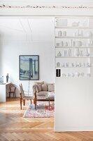 Wohnzimmer hinter Raumteilerregal mit Vasensammlumg