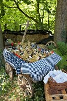 Checked tablecloths and bottles of wine arranged in vintage pull-along cart under tree