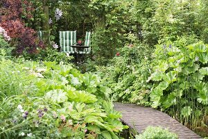 Steg führt durch üppigen Garten zu einem Sitzplatz