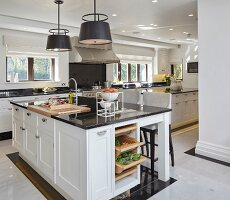 Large black and white kitchen with island counter and classic doors