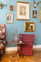 Biedermeier table in front of spotted armchair and blue wall