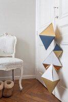 Geometrische Formen aus Papier hängen an Schranktür