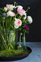 Glasvase mit Bluemstrauss aus rosa Ranunkeln und Anemonen auf Tablett mit Moos