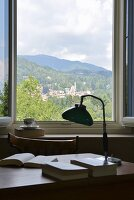 View of hills past vintage-style table lamp and books on desk