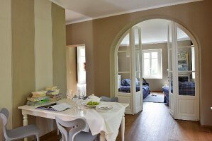 View past dining table through traditional arched doorway into living area of renovated country house
