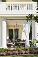 Veranda of villa with enormous pillars and gathered curtains below balcony with postmodern stone balustrade