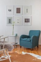 Armchair and side table on castors below gallery of pictures on living room wall