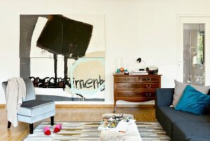 Abstract painting, old chest of drawers and velvet easy chair in living room
