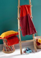 Towel dyed in various shades of red hung over a wooden ladder