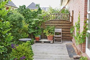 A wooden terrace with green plants and a privacy fence