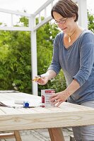 A woman painting a wooden table outside