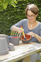 A woman painting flowerpots grey