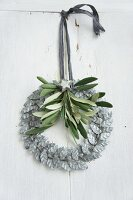 Wreath of silver-grey metal leaves decorated with olive sprig