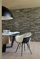 Black and white shell chairs and table in dining area with stone wall