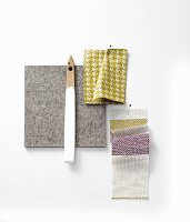 Pinned fabric and colour swatches in grey, grey, white and purple tones